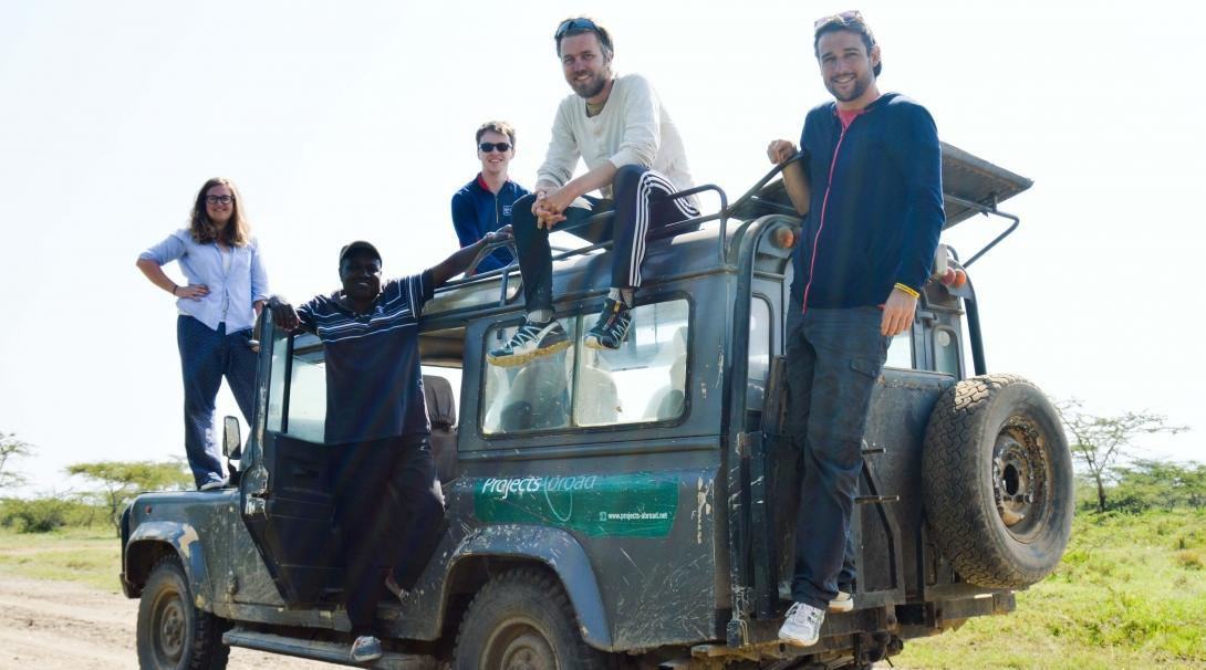 A group of volunteers are pictured on a Jeep truck whilst taking a break from their wildlife conservation volunteering in Kenya with Projects Abroad.